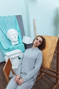 Vrouw die tegen een schildersezel in een kunstruimte leunt