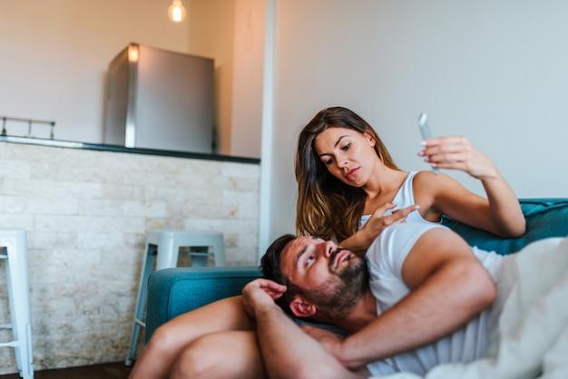 Vrouw die tekstberichten toont aan echtgenoot op zijn mobiele telefoon. affair concept.