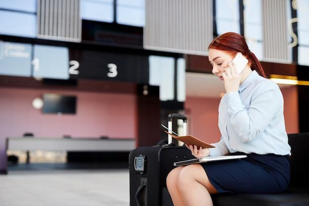 Vrouw die telefonisch in luchthaven spreekt