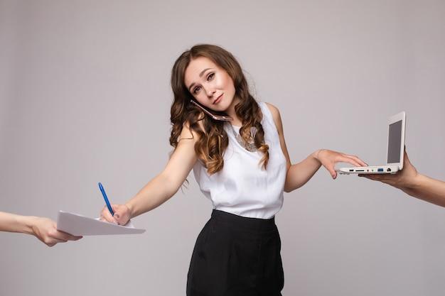 Vrouw die telefonisch spreekt, computer met behulp van en documenten ondertekent