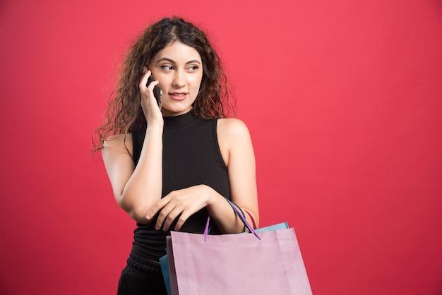 Vrouw die telefonisch spreekt en veel tassen op rood vasthoudt.