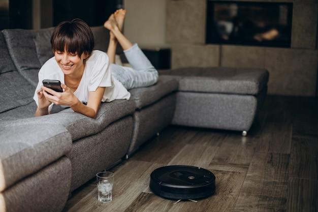 Vrouw die telefoon gebruikt terwijl vacuümrobot de vloer schoonmaakt