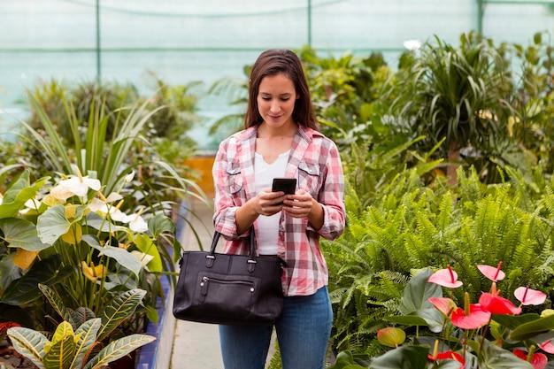 Vrouw die telefoon in serre bekijkt