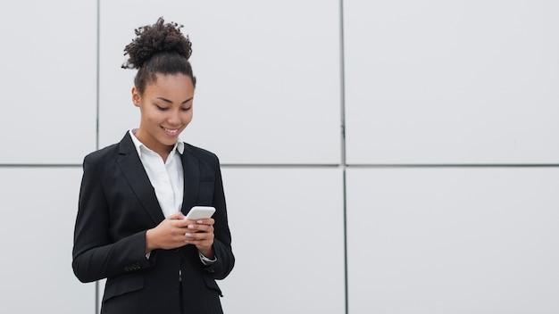 Vrouw die telefoon middelgroot schot controleert