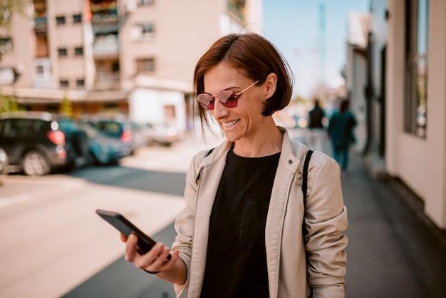 Vrouw die telefoon op de straat met behulp van
