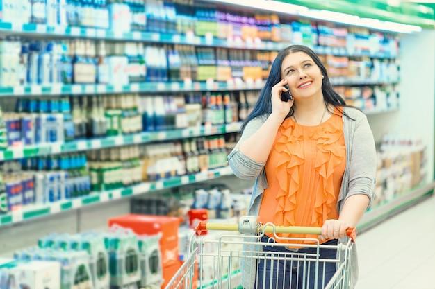 Vrouw die telefoon spreekt en boodschappenwagentje in de supermarktopslag houdt dichtbij het winkelen vensters.