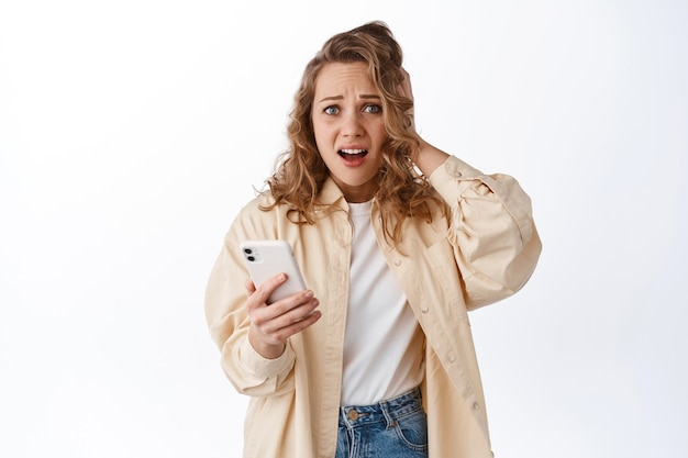 Vrouw die telefoon vasthoudt en in paniek kijkt, zich angstig en bezorgd voelt over iets dat online is gepost, staande met smartphone tegen witte muur