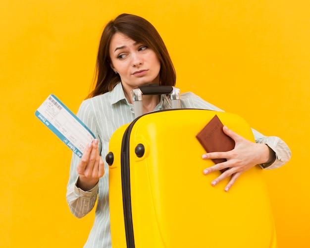 Vrouw die teleurgesteld aan een vliegticket kijkt