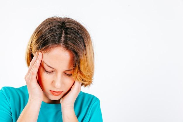 Vrouw die tempels in hoofdpijn wrijft