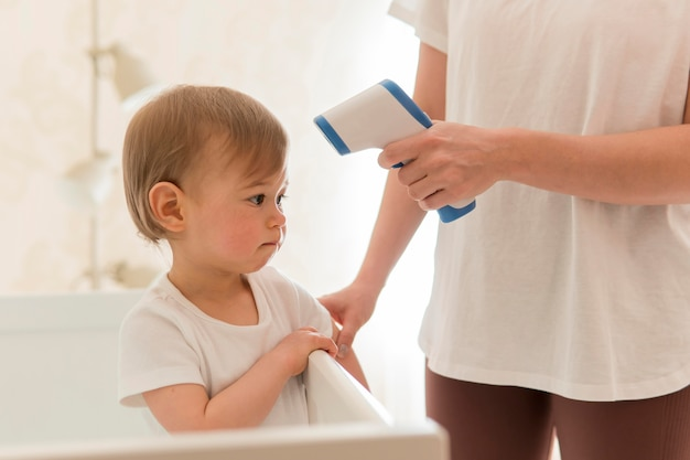 Vrouw die temperatuur van baby controleert