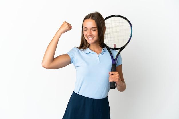 Vrouw die tennis speelt over geïsoleerde witte muur die een sterk gebaar doet