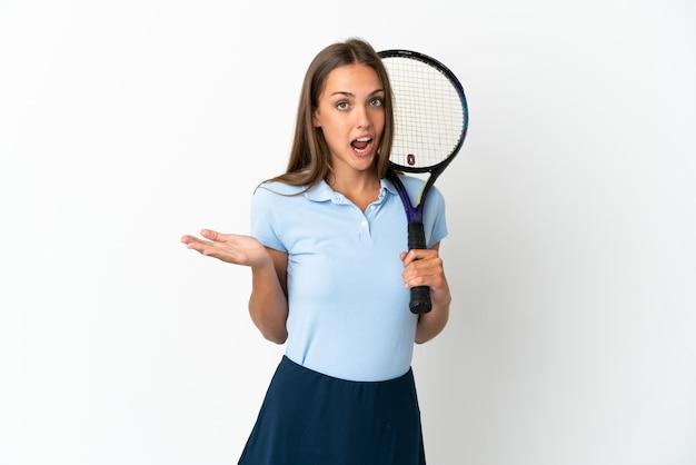 Vrouw die tennis speelt over geïsoleerde witte muur met geschokte gezichtsuitdrukking