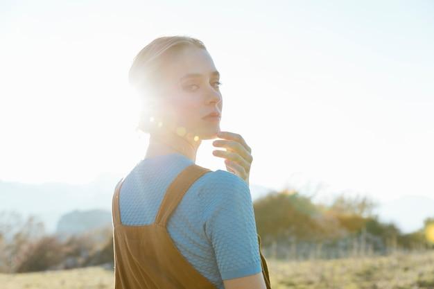 Vrouw die terug over schouder met zonlicht kijkt