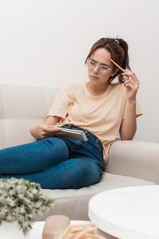 Vrouw die terwijl het bekijken notitieboekje denkt