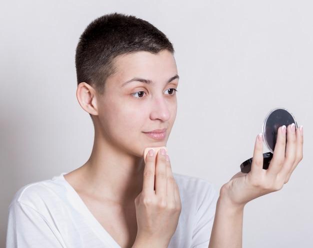 Vrouw die terwijl het bekijken zich in de spiegel schoonmaakt