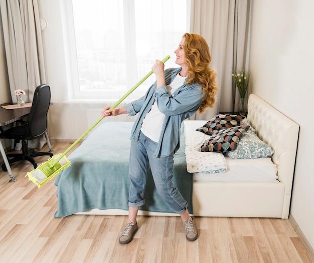 Vrouw die terwijl het dweilen van de vloer zingt