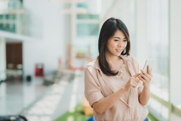 Vrouw die terwijl het gebruiken van smartphone in modern bureau glimlacht