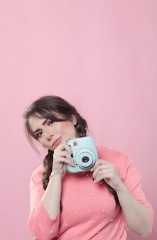Vrouw die terwijl het houden van camera met exemplaarruimte stelt