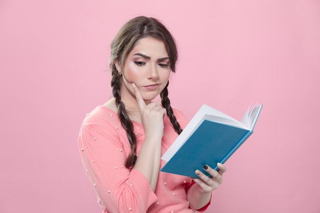 Vrouw die terwijl het houden van een boek denkt