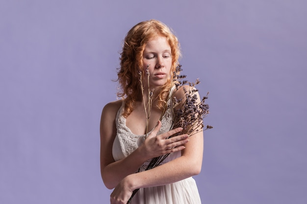 Vrouw die terwijl het houden van een boeket van lavendel stelt