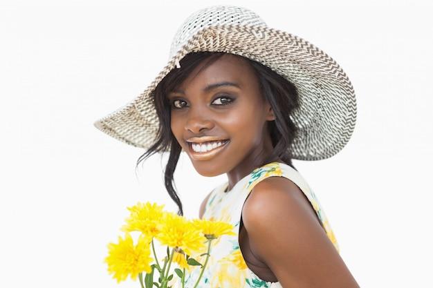 Vrouw die terwijl het houden van gele bloemen bevindt zich