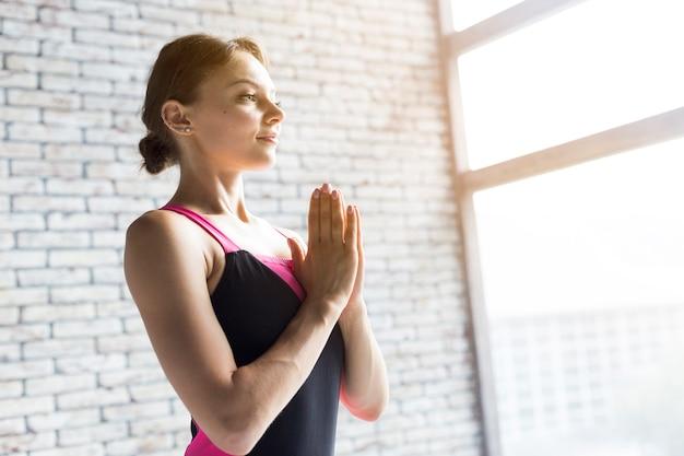 Vrouw die terwijl het houden van handen tegen haar borst ademt