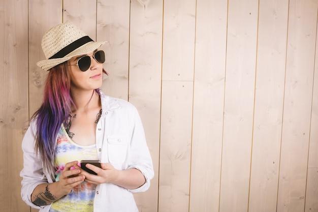 Vrouw die terwijl het houden van mobiele telefoon stelt