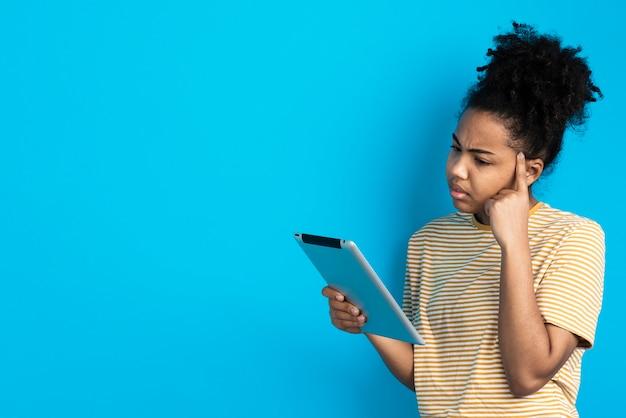 Vrouw die terwijl het houden van tablet denkt