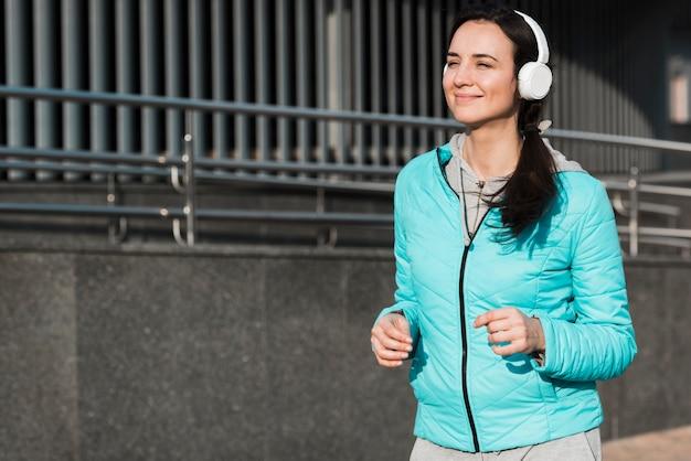 Vrouw die terwijl het luisteren aan muziek door hoofdtelefoons loopt