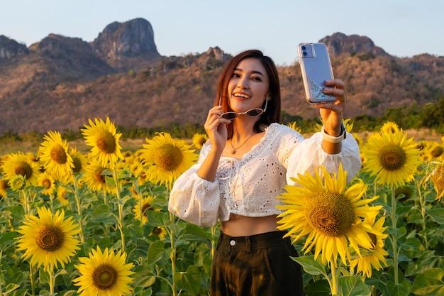 Vrouw die terwijl het nemen van selfiebeeld met mobiele telefoon op zonnebloemgebied in kao jeen lae in lopburi, thailand glimlachen