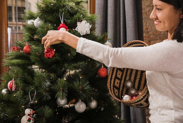 Vrouw die terwijl het verfraaien van de kerstmisboom glimlacht
