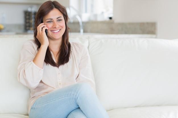 Vrouw die terwijl het zitten op de laag telefoneert