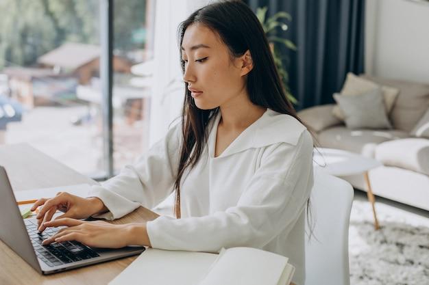 Vrouw die thuis aan de computer aan het bureau werkt