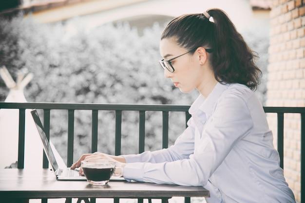 Vrouw die thuis bureauhand aan laptop werkt