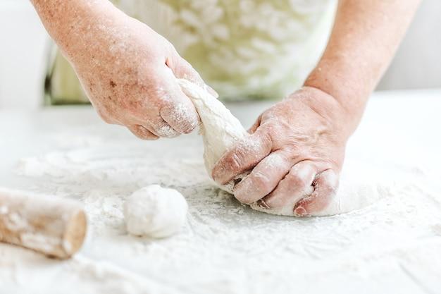 Vrouw die thuis deeg kneedt voor het koken van deegwarenpizza of brood. thuis koken concept. levensstijl