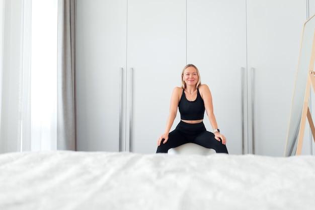 Vrouw die thuis fitnessoefeningen doet met bal