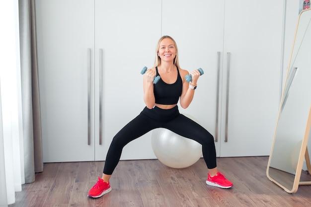 Vrouw die thuis fitnessoefeningen doet met halters