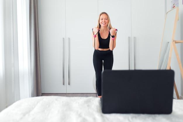 Vrouw die thuis fitnessoefeningen doet met rubber voor fitness