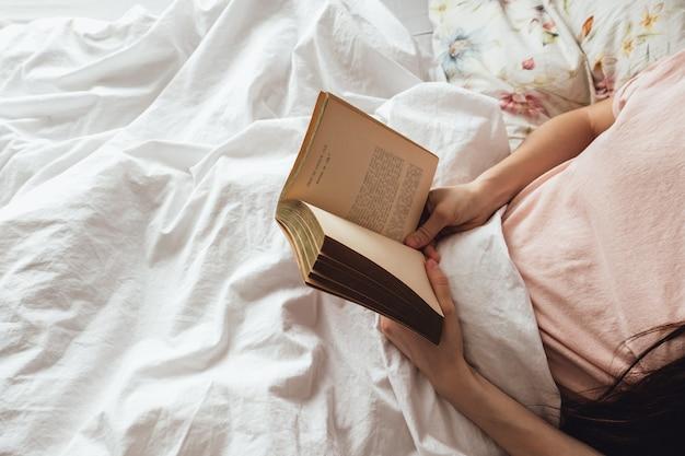 Vrouw die thuis in een wit bed ligt en boek leest.