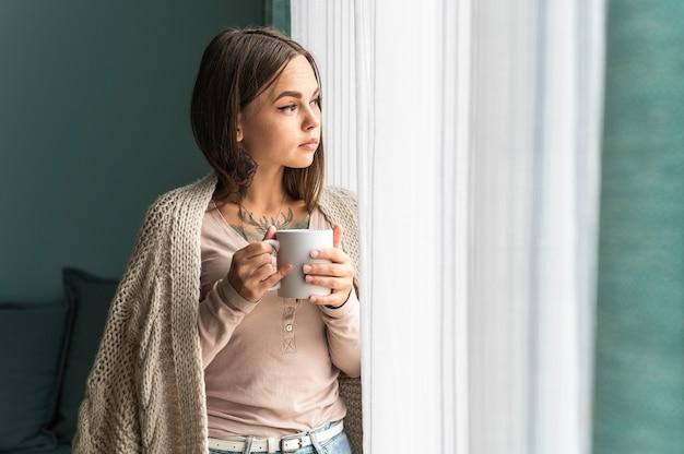 Vrouw die thuis koffie drinkt en door het raam kijkt tijdens de pandemie