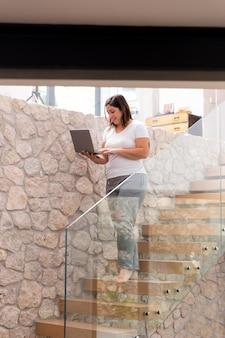 Vrouw die thuis laptop met behulp van