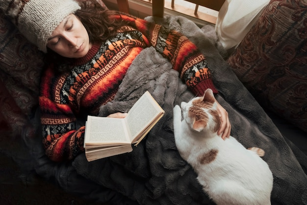 Vrouw die thuis ligt het lezen van een boek dat haar kat aait. concept van hobby's en thuis zijn.