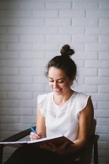 Vrouw die thuis notitieboekje werkende zaken van huis houden.