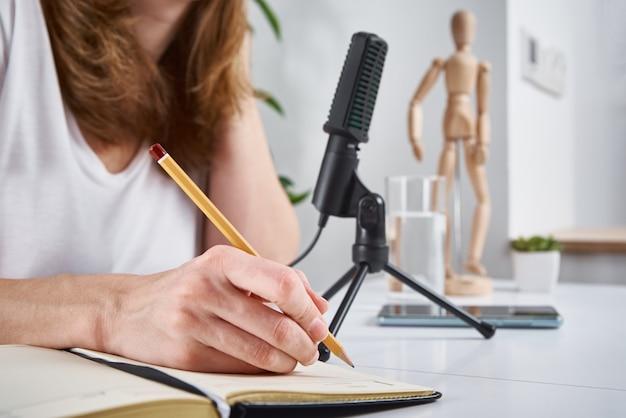 Vrouw die thuis online podcast opneemt. microfoon op tafel, thuisstudio werkplek