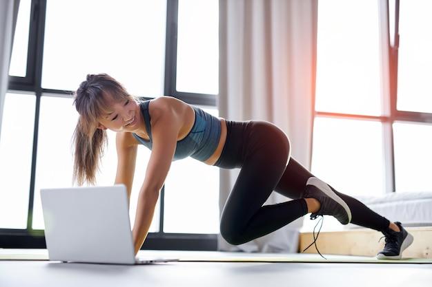 Vrouw die thuis online sportieve oefeningen doet, zelfisolatie is gunstig, vermaak en educatie op internet. gezonde levensstijl concept.