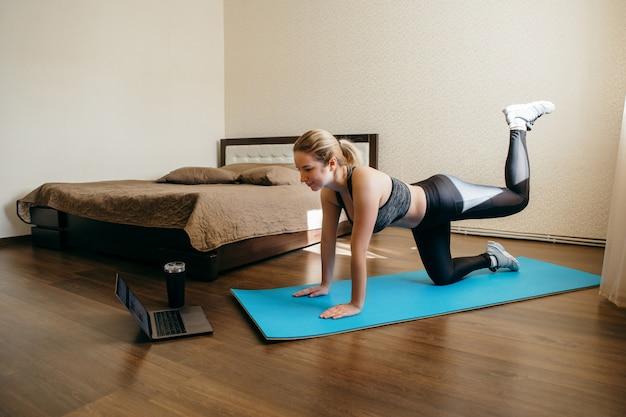 Vrouw die thuis op een yogamat uitwerkt