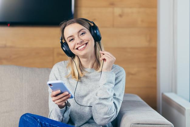 Vrouw die thuis rust en naar leuke muziek luistert op een koptelefoon