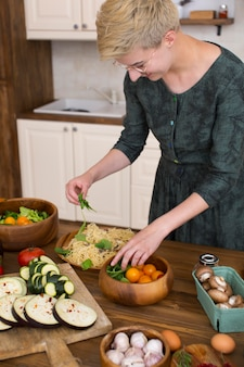 Vrouw die thuis wat gezond voedsel kookt