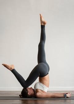 Vrouw die thuis yoga op mat uitoefent