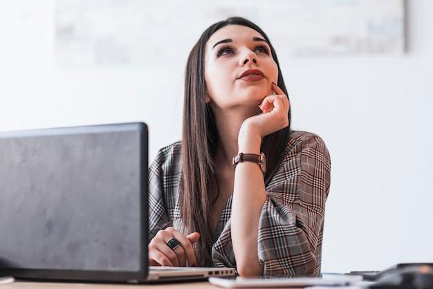 Vrouw die tijdens het werk aan laptop denkt